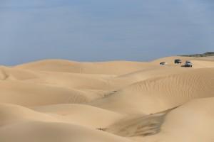 new Range Rover driving through sand dunes, Essaouira, Morocco