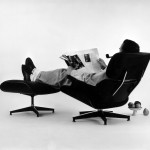 The World of Charles and Ray Eames. Charles Eames in the plywood Lounge and Ottoman, 1956. © Eames Office LLC
